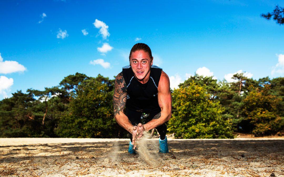 Personal trainer Freek vliegend gefotografeerd tijdens fotoserie in het bos